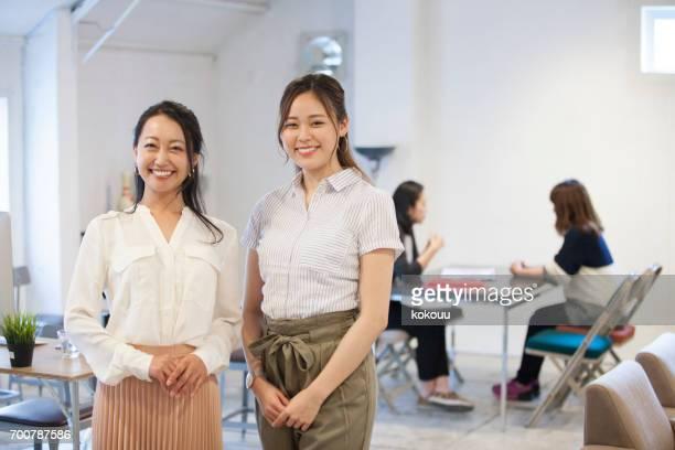 オフィスで微笑む女性たち - 30 34歳 ストックフォトと画像