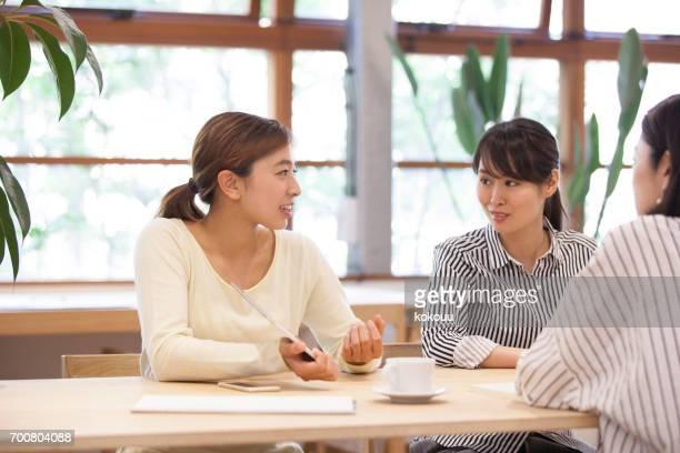 オフィスで仕事をする女性たち - ミーティング ストックフォトと画像