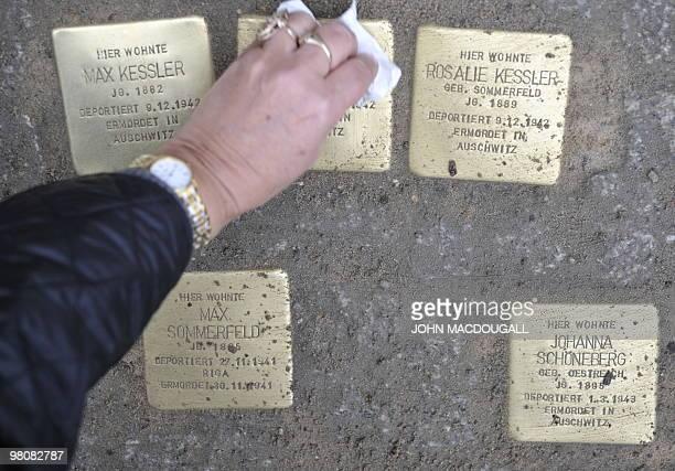 """Women wipes a stolperstein after German artist Gunter Demnig layed """"stolpersteine"""" or stumbling stones in Berlin's Friedrichstrasse March 27, 2010...."""