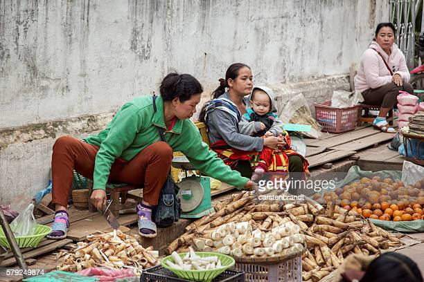 Women with a child selling vegetables in the morning market