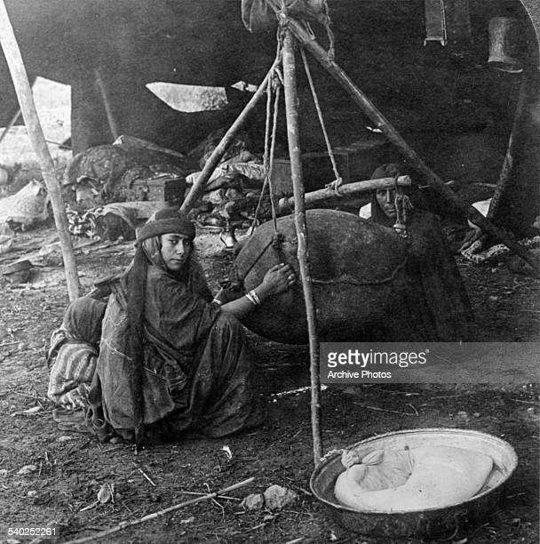 A women with a small child works in a tent in Syria