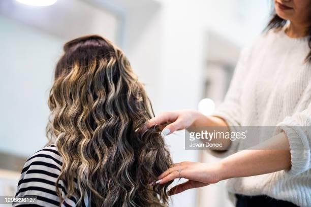 women with beautiful long black hair at treatment in hairstylist salon - penteando imagens e fotografias de stock
