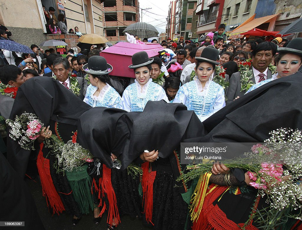 Women with black mantle cry while dancers of the Carnival Troupes Association of La Paz carry on their shoulders a coffin with the traditional figure the 'Cucumber' (el Pepino), near the General Cemetery, inaugurating the carnival celebrations 2013, on January 06, 2013, in La Paz, Bolivia.