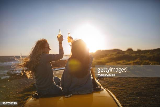 Women with cabriolet car relaxing and drinking soda at beach