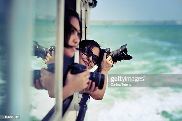 Women with cameras leaning out of boat
