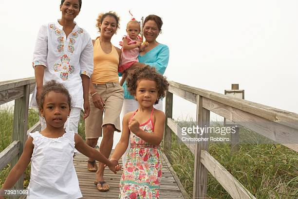 women with children (15 months to 3 years) running down wooden path - 30 39 years foto e immagini stock