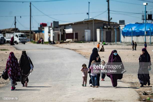 Women with children walk at Camp Roj, where relatives of people suspected of belonging to the Islamic State group are held, in the countryside near...
