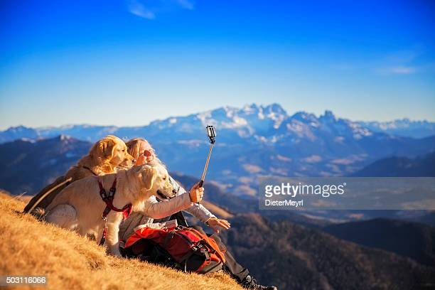Women with dogs  take Selfie with Selfie Stick in Alps
