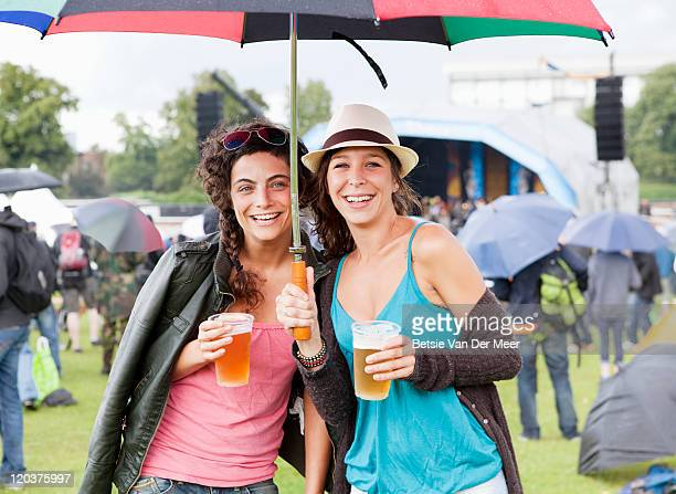 women with drinks under umbrella at music festival
