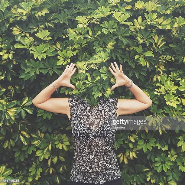 Women with face hidden behind leaves standing with raised arms
