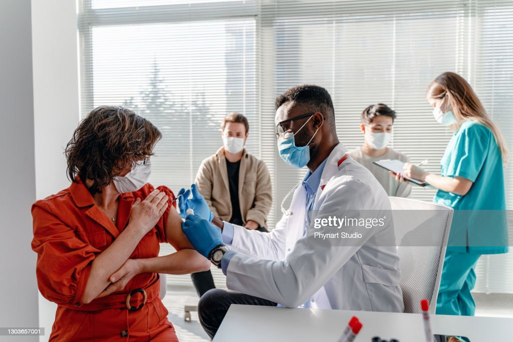 women with face mask getting vaccinated, coronavirus, covid-19 and vaccination concept : Stock Photo