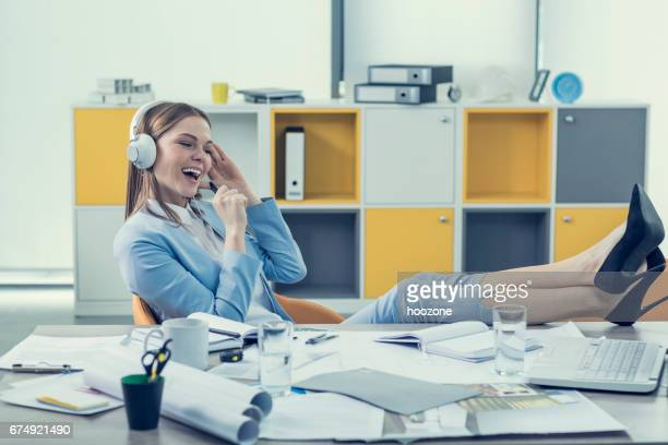 Women with feet up on desk listening music on headphones and singing at office