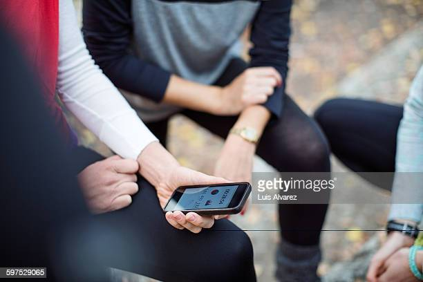 Women with female friend holding smart phone