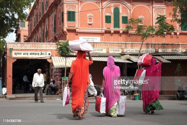 Women with goods purchased from old market pass the UNESCO World Heritage Site walled city of Jaipur on July 7 2019 in Jaipur India The Walled City...