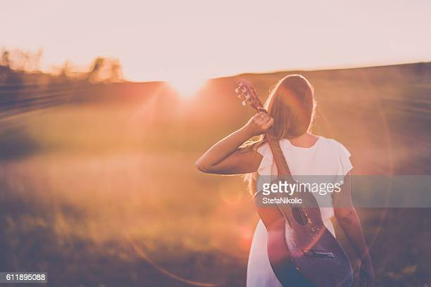 Women with guitar over sunset sky