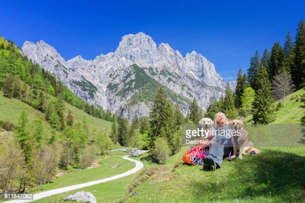 women with her retriever dogs enjoy the view  in nationalpark berchtesgaden - berchtesgaden stock photos and pictures