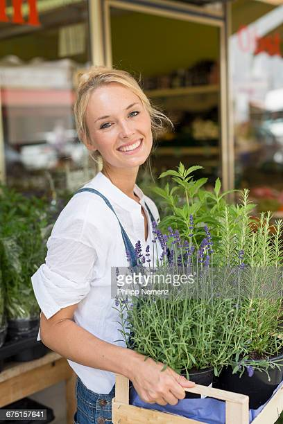 women with herbs in fornt of store