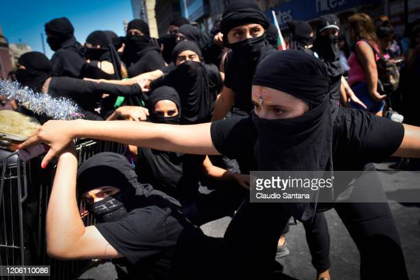 Women with masks perform during protests as part of the International Women's Day on March 8 2020 in Santiago Chile