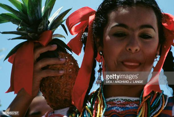 Women with pineapples and wearing traditional costumes during the celebrations at the Guelaguetza festival Oaxaca Mexico