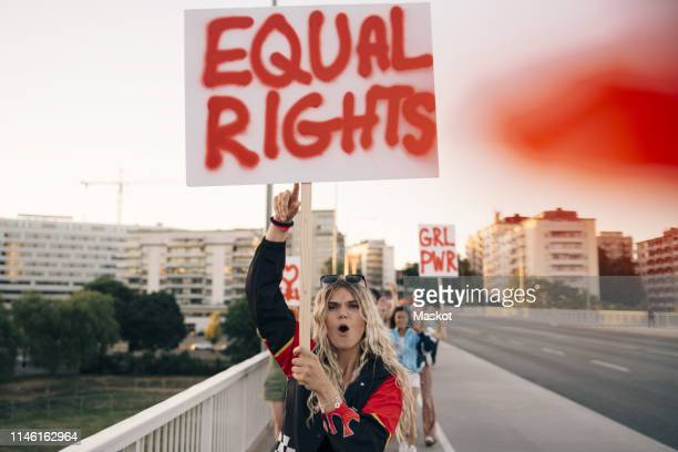 women with poster shouting while marching for equal rights on bridge in city - march stock-fotos und bilder