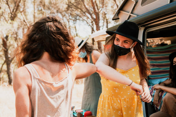 Women with protective masks greeting with ellbows during camper van trip