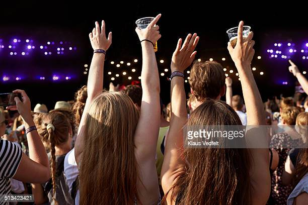 Women with raised hands holding beer at concert
