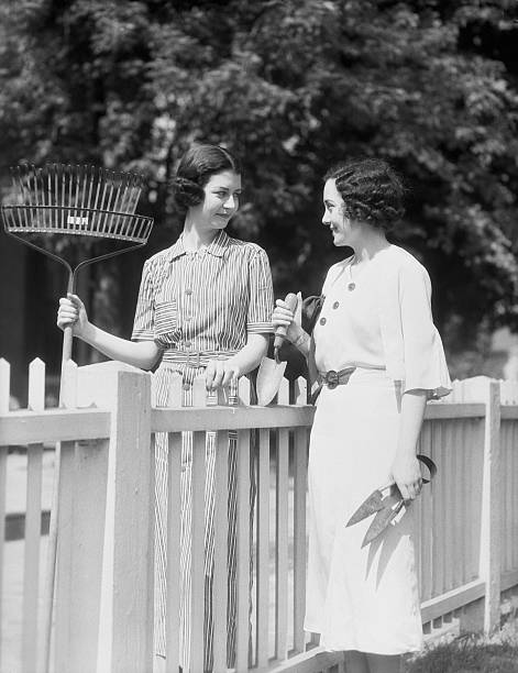 Women with rake clippers and trowel chatting over picket...