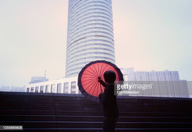 Women with red umbrella in front of city skyline