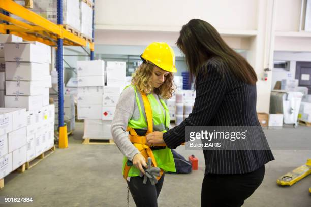 women with safety harness in warehouse