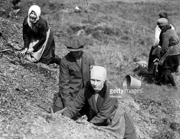 Women with scarves round their heads search a spoil heap near Manchester for fuel during the general strike 1926