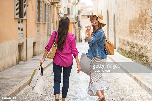 women with shopping bags on street, palma de mallorca, spain - long dress stock pictures, royalty-free photos & images