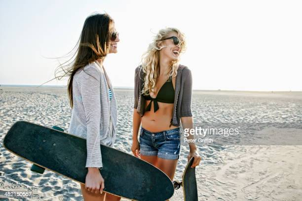 Women with skateboards standing on beach