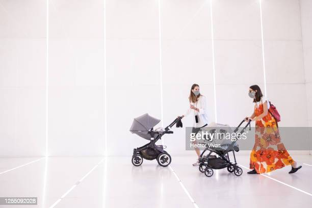 Women with strollers wearing face masks enter through the main entrance of the mall at Antara Shopping Mall on July 08, 2020 in Mexico City, Mexico....
