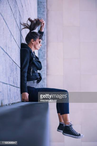 women with sun glasses sitting on ledge - irony stock pictures, royalty-free photos & images