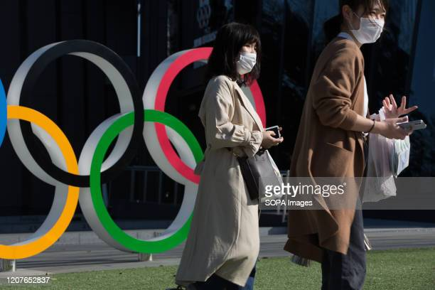 Women with surgical masks walk next to the Olympic Rings in front of the Japan Olympic Museum in Shinjuku. Japanese start thinking that it would be...