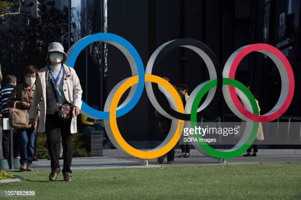 Women with surgical masks walk next to the Olympic Rings in front of the Japan Olympic Museum in Shinjuku Japanese start thinking that it would be...