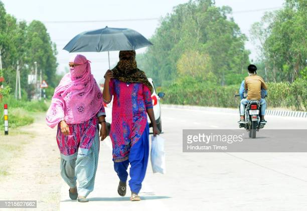Women with their faces covered walk under an umbrella for shade on a hot summer day on May 27, 2020 in Patiala, India.