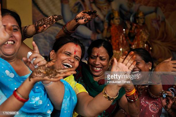 Women with their hands decorated with henna celebrate Teez festival at temple on August 1 2013 in Noida India Hindu festival of Teej is to herald the...