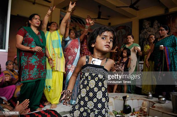Women, with their hands decorated with henna celebrate Teez festival at temple on August 1, 2013 in Noida, India. Hindu festival of Teej is to herald...