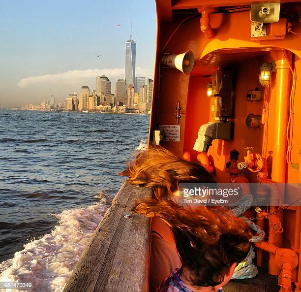 women with tousled hair sitting in staten island ferry boat against city - staten island ferry stock pictures, royalty-free photos & images
