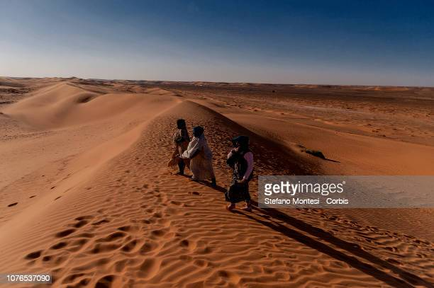 Women with traditional dress Saharawi in the Sahara desert near the Saharawi refugee camp Dakhla on December 31, 2018 in Tindouf, Algeria.