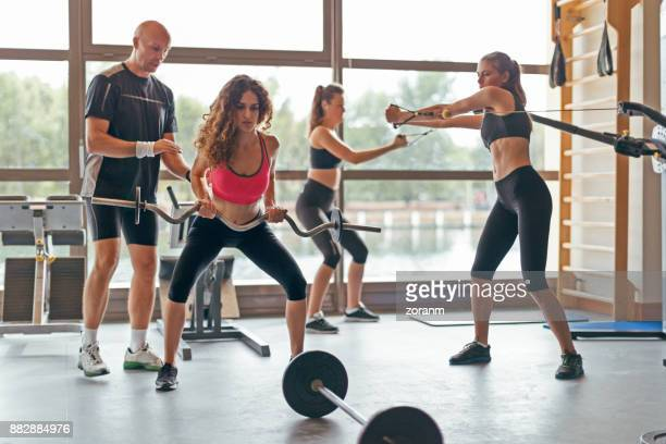 Women with trainer in gym