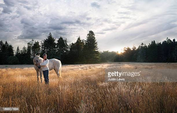 Women with white horse in forest meadow at sunrise