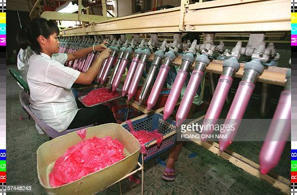Women work at a condom testing line in the Medical Rubber Factory in HoChiMinhCity 26 May The media has begun adivsing people to protect themselve...
