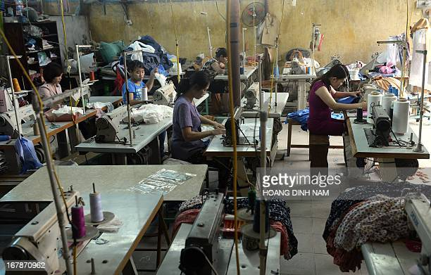 Women work at a small size garment workshop on the outskirds of Hanoi on May 2 2013 From factory fires to slave labour the growth of mass...