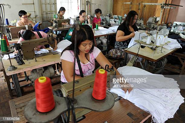 Women work at a sweatshop sewing clothes under contract with local clothing manufacturers in Manila on July 12 2013 Visiting World Bank vice...