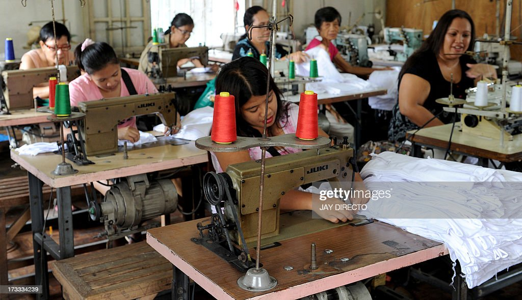 Women Work At A Sweatshop Sewing Clothes Under Contract