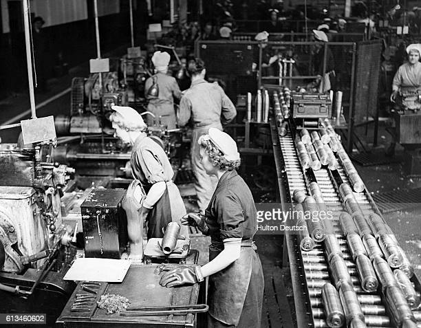 Women work at an armaments factory in Wigan England in 1951 An inspector examines shells as they move along the assembly line