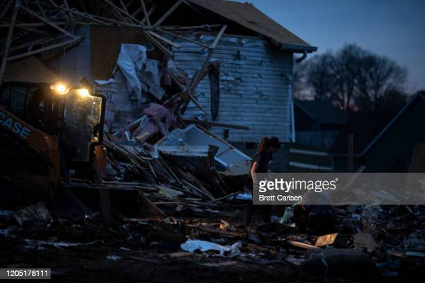 Women work by the light from machinery as they clean debris outside a tornado damaged home on March 4 2020 in Cookeville Tennessee A tornado passed...