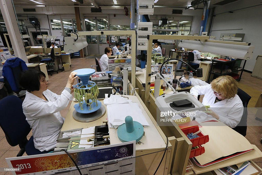 Women work on plastic models of turbine blades, on January 14, 2012 at the Safran - Snecma plant in Gennevilliers, near Paris.